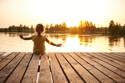Silhouette of a child sitting on the wooden pier and enjoying heat summer evening at the lake at sunset. Heat summer, summer evenings in nature, spending time in the fresh air