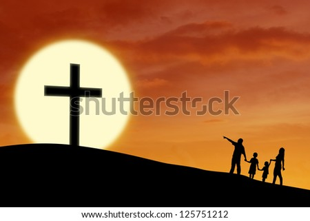 Silhouette of a Christian family walking toward Cross sign during sunset