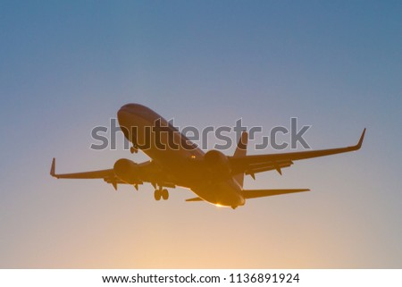 silhouette of a civilian aircraft at sunset