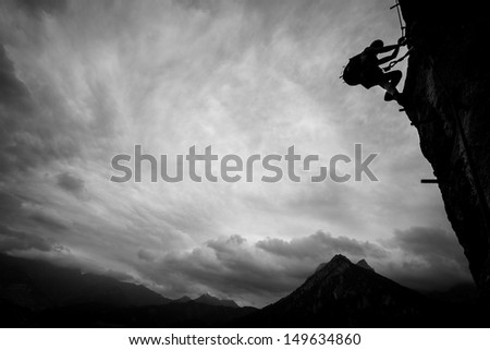 Silhouette of a climber above mountain peaks