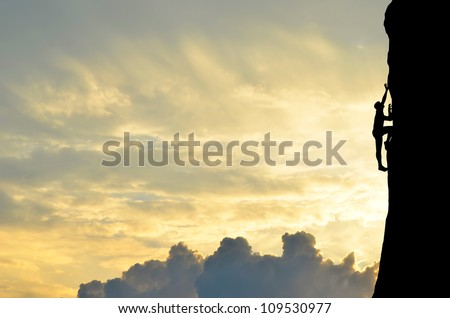 silhouette of a climber conquers the top of a steep hill