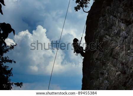 Silhouette of a climber hanging on a rope by cliff with blue stormy clouds on the background