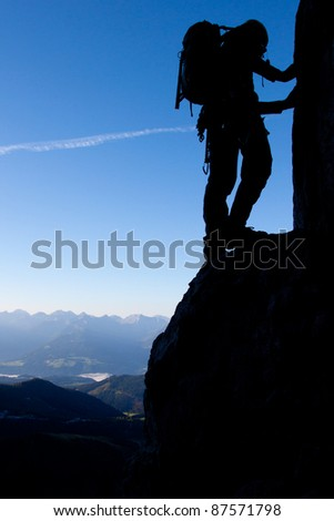 Silhouette of a climber high above valley