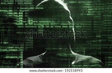 Silhouette of a computer hacker with binary codes from monitor