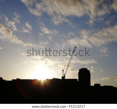 Silhouette of a construction tower crane on a building against a dramatic sunset with sunlight lens flare.