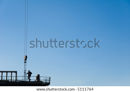 silhouette of a construction worker working with a crane