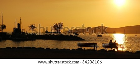 Silhouette of a couple enjoy beautiful sunset view in English Bay, Vancouver Canada - stock photo