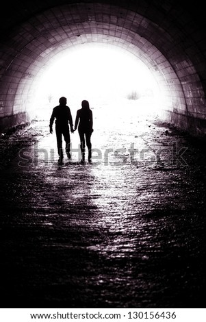 Silhouette of a couple holding hands and walking together in darkness
