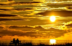 Silhouette of a couple on a bench against the sunset. Sunset sky clouds. Cloudy evening sky at sunset. Sunset romantic scene