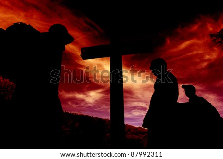 silhouette of a cross against red sky, with people in return of it,