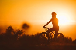 Silhouette of a cyclist man riding mountain bike on a mountain at sunset.