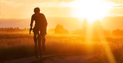 Silhouette of a cyclist on a gravel bike riding a trail in a field on a dramatic sunset background.