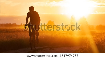 Photo of  Silhouette of a cyclist on a gravel bike riding a trail in a field on a dramatic sunset background.