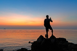 Silhouette of a dog and man with a backpack standing on the rock by the sea at sunset and taking pictures on a smartphone