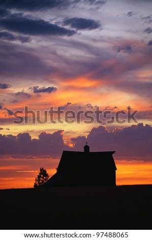 Silhouette of a farm at sunset with a pinkish, orange glow in the sky