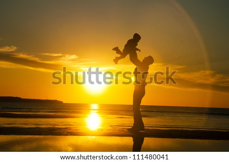 Silhouette of a father and a child playing on the beach