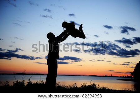 Silhouette of a father lifting up his daughter in the sunset