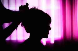 Silhouette of a female head and a hairdresser hands on a background of purple curtains.