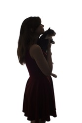 silhouette of a figure of a young girl with a cat in her arms looking forward, pets concept