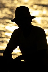 Silhouette of a fisherman against sunset lights and calm coastal waters