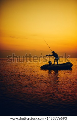 Silhouette of a fisherman fishing in sunset time on the open sea. #1453776593