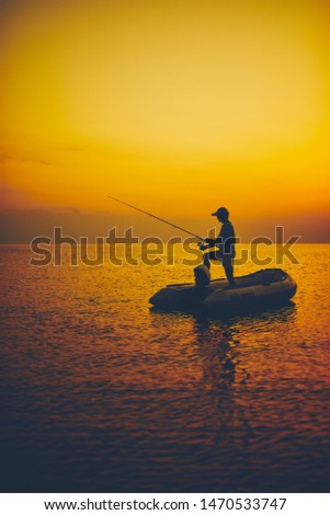 Silhouette of a fisherman fishing in sunset time on the open sea. #1470533747