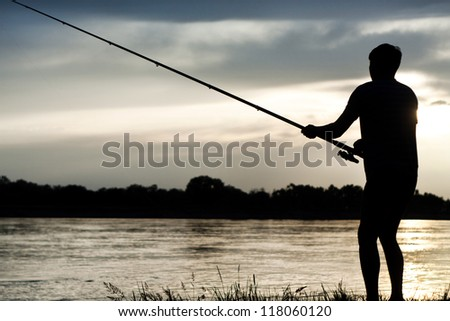 silhouette of a fisherman with a fishing rod in the river at sunset