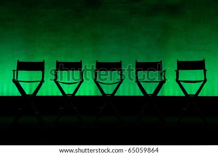 Silhouette of a five traditional wood and canvas Director\'s Chair on a green stage background