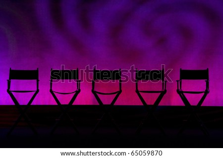 Silhouette of a five traditional wood and canvas Director\'s Chair on a purple swirls stage background