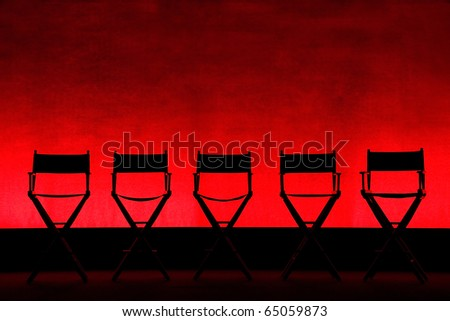 Silhouette of a five traditional wood and canvas Director\'s Chairs on a red stage background - horizontal