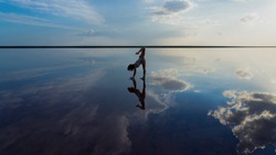 Silhouette of a flexible graceful girl in the mirror reflection of the sky and sea, handstand in harmony with nature