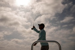 Silhouette of a fly fisherman casting with a bright cloudy sky in the background on Ambergris Caye island, Belize.