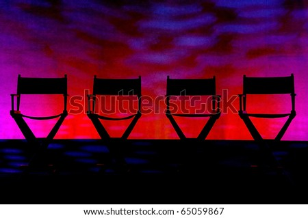 Silhouette of a four traditional wood and canvas Director\'s Chair on a red and purple stage background