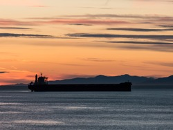 Silhouette of a freighter at sea with a sunset as a background. Freighters move commodities around the world.