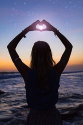 Silhouette of a girl at sky with stars near ocean holding heart - shape sign with hands. My astronomy work.