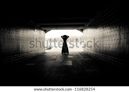Silhouette of a girl on bright background at the end of an underground pedestrian tunnel