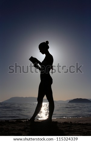 silhouette of a girl reading a book at the beach