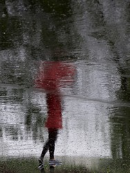 Silhouette of a girl standing in the street in red jacket holding red umbrella. Creative photo of rain mood. Woman's reflection on a wet pavement after the rain