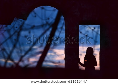 Silhouette of a girl with a candle in windowed ancient openings. Dark photo, view of the sunset in the background. Art photo among the ancient ruins. Mysterious mysterious situation.  #611615447