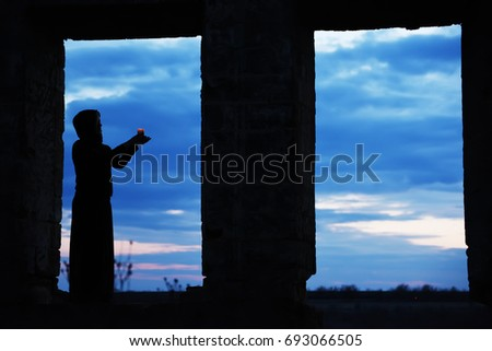 Silhouette of a girl with a candle in windowed ancient openings. Dark photo, view of the sunset in the background. Art photo among the ancient ruins. Mysterious mysterious situation.  #693066505