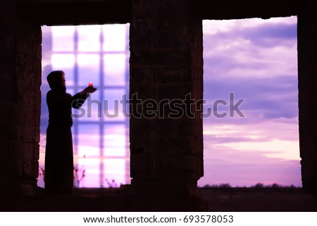 Silhouette of a girl with a candle in windowed ancient openings. Dark photo, view of the sunset in the background. Art photo among the ancient ruins. Mysterious mysterious situation. #693578053