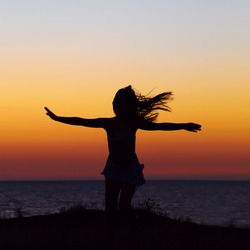 silhouette of a girl with flying hair and arms outstretched on the sea background. sunset outdoors. summer child