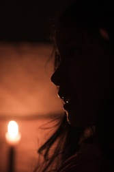 Silhouette of a girl with long hair created from candlelight in the dark.