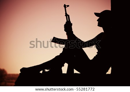 Silhouette of a girl with the Kalashnikov machine gun in the doorway.