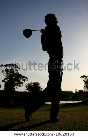 Silhouette of a golfer on the tee box with driver