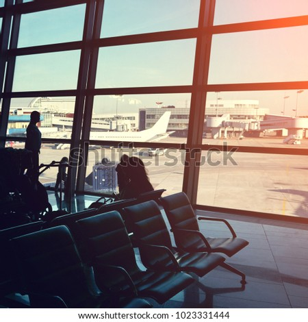 silhouette of a group of people in an airport waiting hall. travel business concept #1023331444