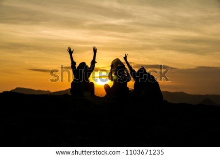 Silhouette of a group of women on hill top with arms raised celebrating their success hiking the Merese hill in Lombok Indonesia. #1103671235