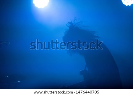 Silhouette of a guitarist in blue stage lights