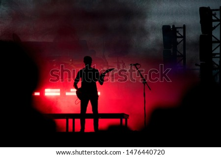Silhouette of a guitarist in red stage lights