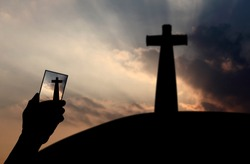 Silhouette of a hand holding a smartphone taking photo of a Christian crucifix against a surreal sunrise for the concept: Smartphone is the new religion.